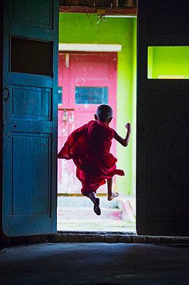 Young monk dances out of class; Yangoon, Myanmar - p442m1033860 by David Kirkland