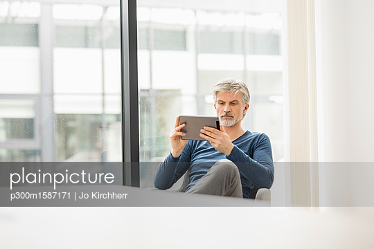 Mature man sitting in his office, using digital tablet - p300m1587171 von Jo Kirchherr