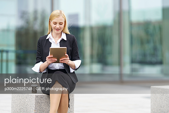 Blond businesswoman using digital tablet while sitting on bench against building - p300m2225748 by GER photography