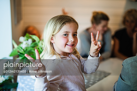 Girl making peace sign - p312m2139455 by Anna Johnsson