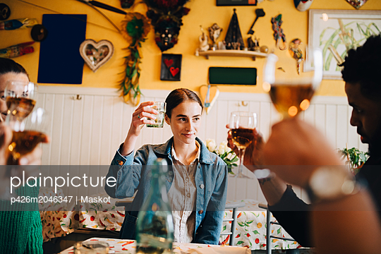 Young woman raising celebratory toast while sitting with multi-ethnic friends at dinner party in restaurant - p426m2046347 by Maskot