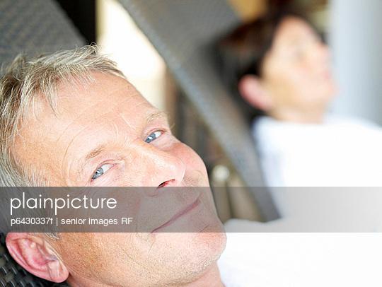 Aelterer Mann in weissem Bademantel auf einem Liegestuhl  - p6430337f von senior images RF