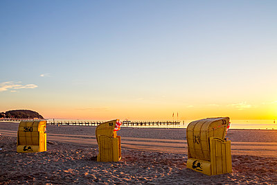 Germany, Schleswig-Holstein, Timmendorfer Strand, hooded beach chairs and sea bridge in the evening - p300m1549452 by pure.passion.photography