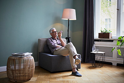 Mature man using cell phone at home - p300m2030160 by Rainer Berg