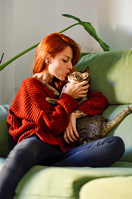 Red-haired woman with cat on couch at home - p300m2132041 by Javier Sánchez Mingorance