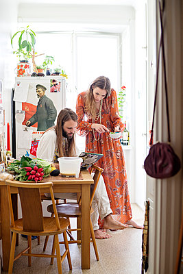 Young couple in kitchen - p312m992849f by Cecilia Moller