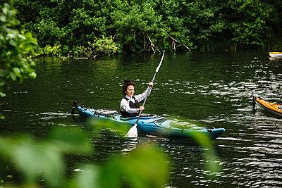 Senior woman paddling kayak in sea during kayaking course - p426m2149390 by Maskot