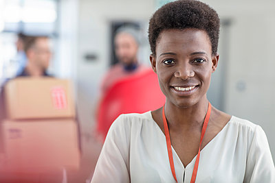 Portrait of woman in office looking at camera smiling - p924m1513399 by Zero Creatives