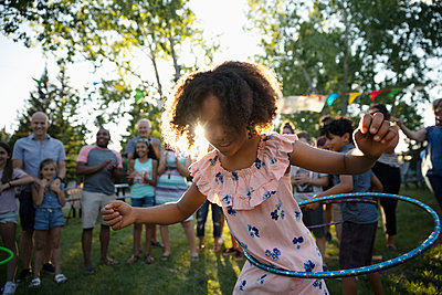 Playful girl spinning in plastic hoop at summer neighborhood block party in park - p1192m2017041 by Hero Images