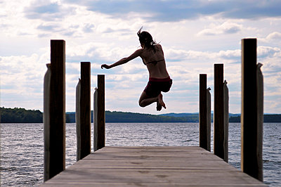 Girl Jumping off Boardwalk - p1304m1136832 by MY MY