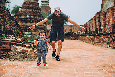 Thailand, Ayutthaya, Father and daughter running in the ancient ruins of a temple at Wat Mahathat - p300m2058731 by Gemma Ferrando
