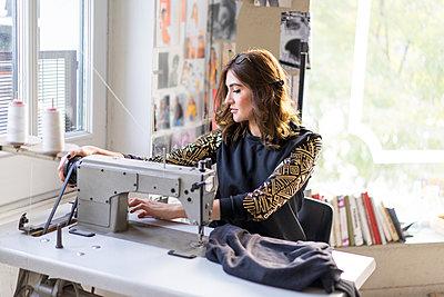 Young designer using sewing machine in an atelier - p300m2068730 von VITTA GALLERY