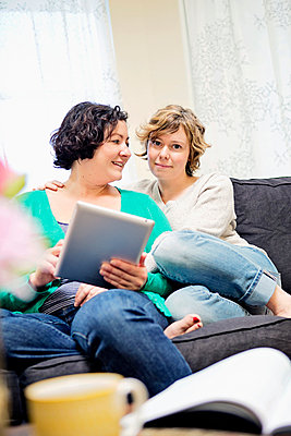 Lesbian couple using digital tablet on sofa in living room - p555m1409076 by Shestock