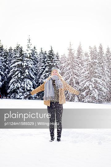 Junge Frau spielt mit Schnee - p1124m1589329 von Willing-Holtz