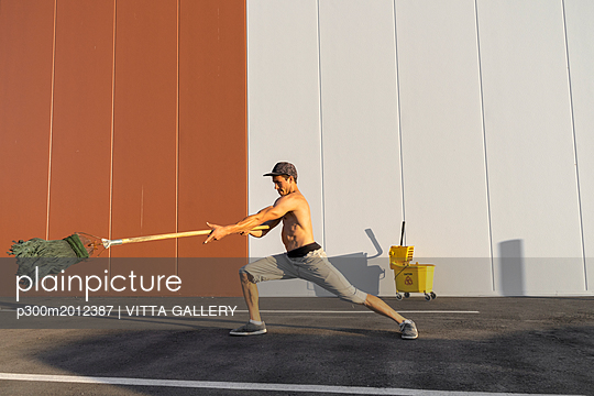 Acrobat playing with cleaning bucket and mop - p300m2012387 von VITTA GALLERY