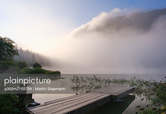 Germany, Bavaria, Mittenwald, Jetty on lakeshore of Ferchensee at misty sunrise - p300m2155759 by Martin Siepmann