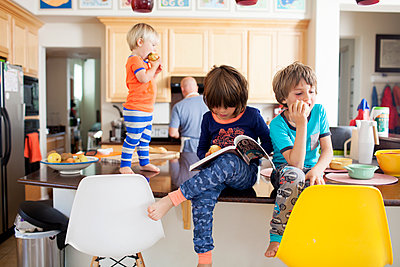 Boys eating apples at kitchen counter while father working in kitchen - p1166m1186798 by Cavan Images