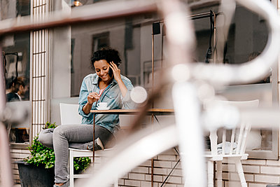 Young woman drinking coffee in front of cafe, talking on the phone - p300m2012745 by Kniel Synnatzschke