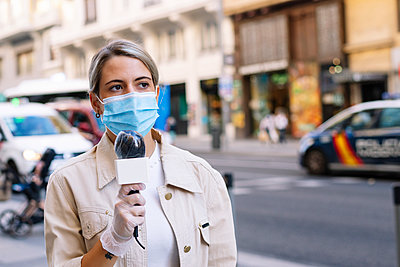 Female journalist wearing mask with microphone looking away while standing on street in city - p300m2221009 by Jose Luis CARRASCOSA