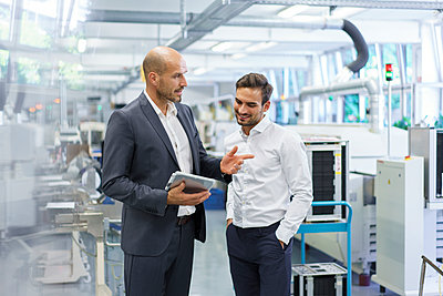 Confident businessman discussing with engineer over digital tablet at factory - p300m2221249 by Robijn Page