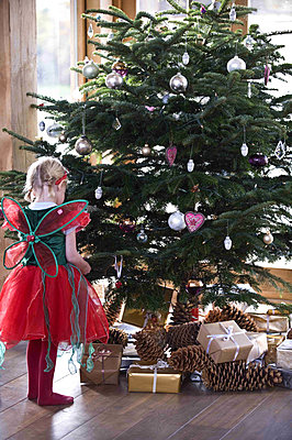 Young girl dressed up looking at the Christmas tree - p349m790660 by Polly Eltes