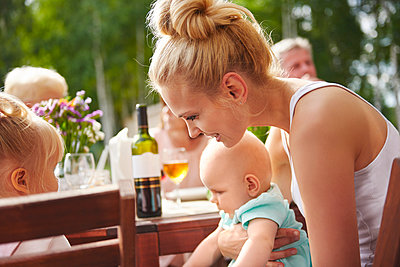 Young woman with baby and toddler daughters at patio table family lunch - p429m1494219 by Gpointstudio