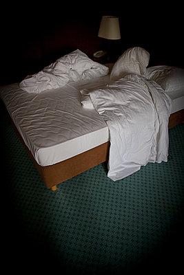 zerwuehltes bett in einem hotelzimmer - p627m1035233 von Chris Keller