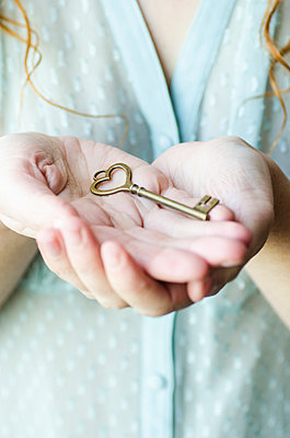 Woman holding a heart shaped key  - p794m1026549 by Mohamad Itani