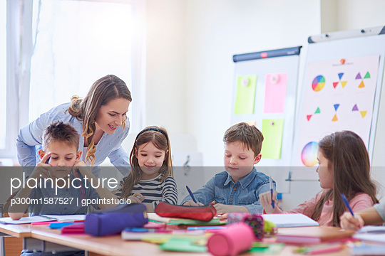 Smiling teacher helping pupils with their tasks in class - p300m1587527 von gpointstudio