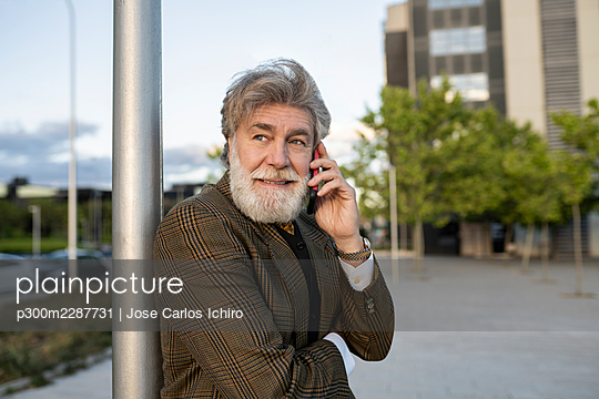 Mature businessman leaning on pole while talking through mobile phone in city - p300m2287731 by Jose Carlos Ichiro