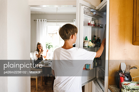 Pre-adolescent boy opening refrigerator door while standing in kitchen - p426m2238102 by Maskot