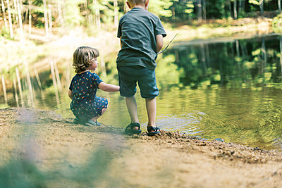 Two siblings playing by the pond together - p1166m2205699 by Cavan Images