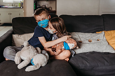 Young girl and school-age boy with masks hugging and smiling on couch - p1166m2207782 by Cavan Images