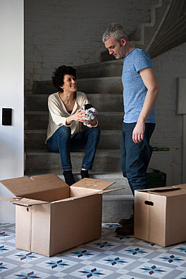 A mixed age couple packing moving boxes - p301m799689f by Halfdark