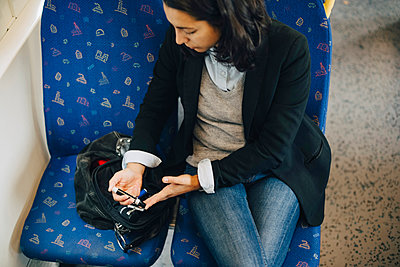 Woman doing blood test while traveling in train - p426m1537166 by Maskot