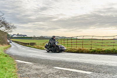 Senior man and grandson riding motorcycle and sidecar on rural road - p429m1227271 by GS Visuals