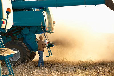 farmer with combine tractor in action; three hills, alberta, canada - p44213136 by Ron Nickel