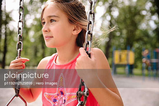 Portrait of young girl sitting on swing looking away - p1192m2129899 by Hero Images