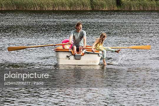 Father and daughter rowing together - p294m2206277 by Paolo