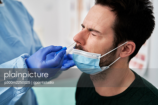 Medical professional collecting sample using nasal swab for COVID-19 test - p300m2250025 by gpointstudio