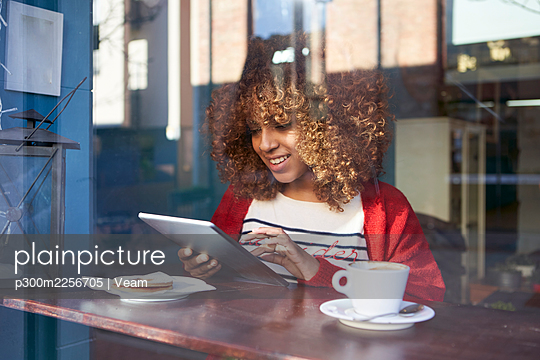 Smiling Afro woman using digital tablet while sitting at cafe - p300m2256705 by Veam