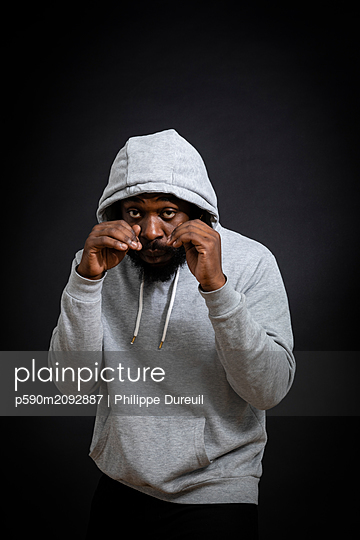 Black man with a sweat shirt boxing - p590m2092887 by Philippe Dureuil