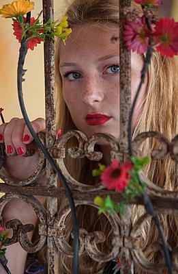 Frau blickt durch Gittertür - p045m1586189 von Jasmin Sander