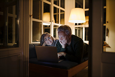 Happy senior couple lying on couch at home at night using laptop - p300m2155268 by Gustafsson