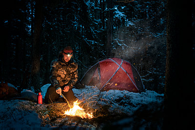 Man at log fire in winter forest - p312m2292273 by Hans Berggren