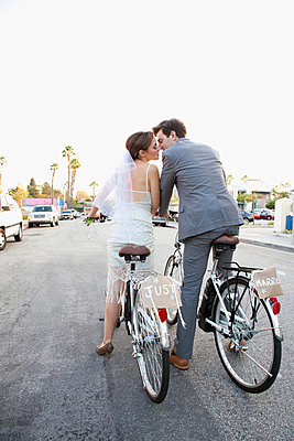 Young newlywed couple kissing on bicycles in street - p92412057 by Steven Lam