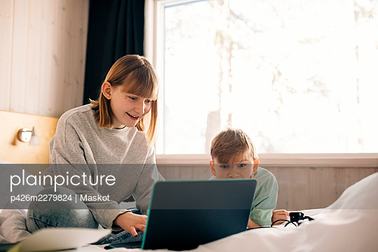 Smiling girl with brother using laptop in bedroom at home - p426m2279824 by Maskot