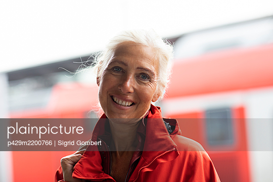 Portrait of smiling woman with long white hair, looking at camera. - p429m2200766 by Sigrid Gombert