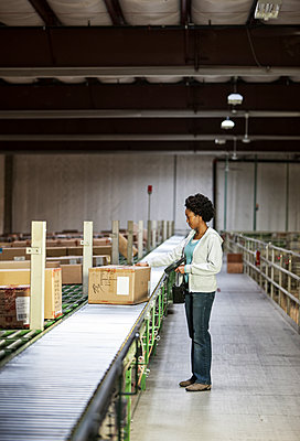 African American female  warehouse worker in a large distribution warehouse, showing products stored in cardboard boxes, and moving on a motorized conveyor system. - p1100m1575473 by Mint Images