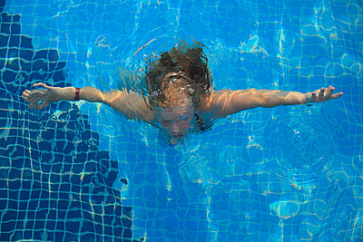 Girl diving in a pool - p2430470 by Claudia Anys